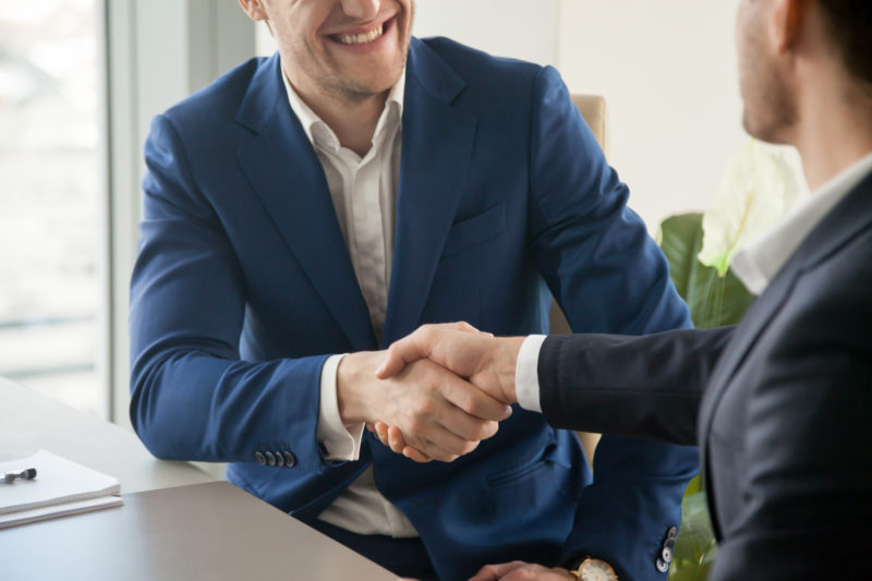 Businessman in blue suit handshaking at business meeting | 5 Reasons Why Good Employees Leave